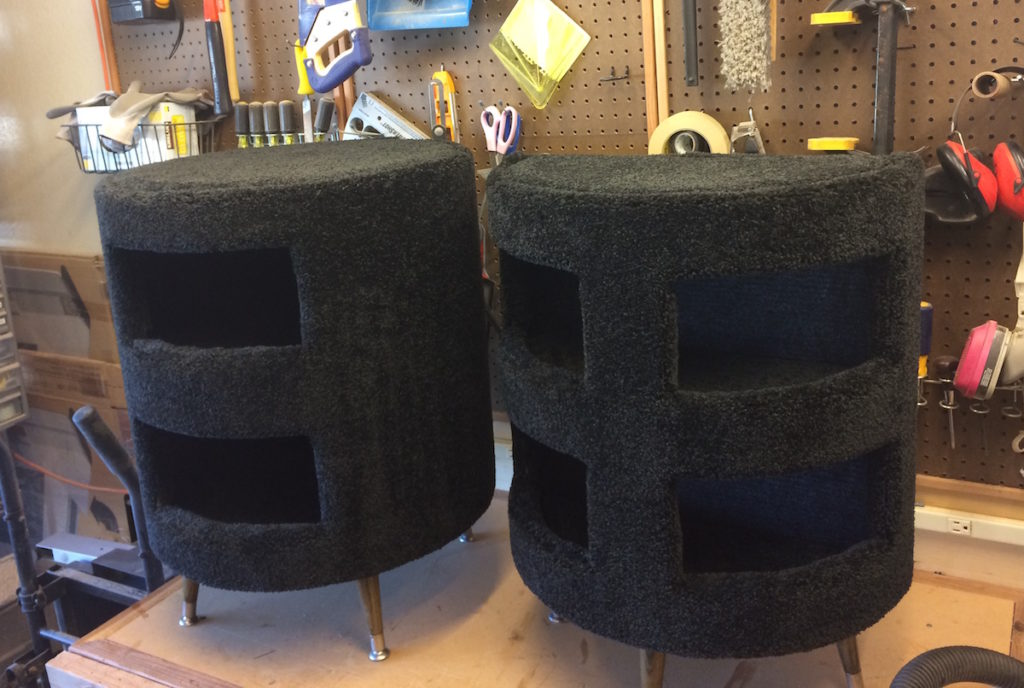 Two black carpeted cat condos side by side on a work bench